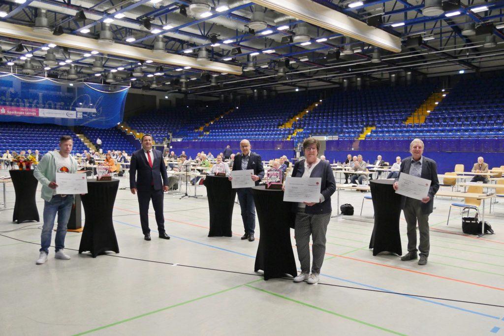 BUZ: Verleihung auf der Spielfläche der Phoenix Contact Arena (v.li): Florian Schalofsky (Platz 2), Landrat Dr. Lehmann, Olaf Henning (Platz 1), Ilsemarie Büscher (Platz 3) und Günther Wiemann (Sonderpreis).